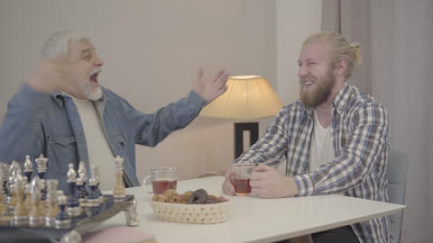 Two cheerful Caucasian men laughing and drinking tea indoors. Happy young son Live Action