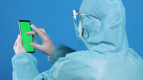 Medical worker with protective gloves uses the phone Live Action