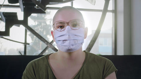 Bald girl is sick with cancer. Woman puts on a medical protective mask. Protects Live Action
