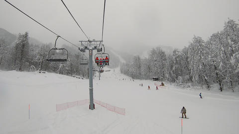 Timelapse transportation on rope way in winter resort. Point view people riding on ski lift. Skiers Live Action