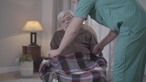 Adult male nurse covering sleeping retiree with blanket and leaving. Portrait of Live Action