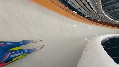 Athlete sliding on luge in ice centre. Rider in bodysuit and helmet riding sled inside slide. Winter Live Action