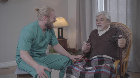 Portrait of joyful old man joking and laughing out loud with male nurse indoors Live Action