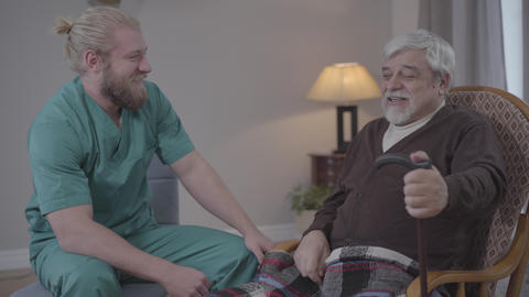 Side view of positive male nurse and retiree talking and laughing. Caucasian Live Action