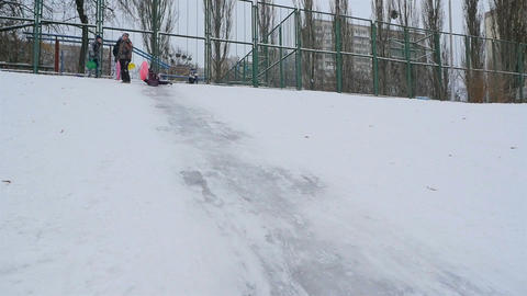 Funny girl goes down a snowy hill. Slow motion Slow motion 01.10.2020 Ukraine Live Action
