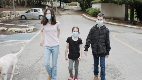 Coronavirus pandemic - kids walking outdoors with face masks to avoid corona Live Action