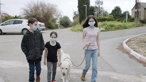 Coronavirus pandemic - kids walking outdoors with face masks to avoid corona Live Action