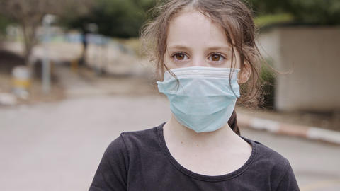 Coronavirus pandemic close up on girl face wearing face mask to avoid contagion Live Action
