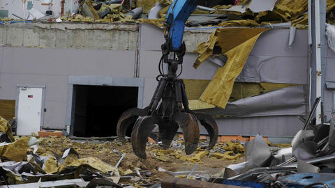 machine with robotic arm disassembles rubble of hokey arena Live Action