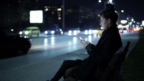 Lonely woman sitting at night at highway with cars rushing past her Live Action