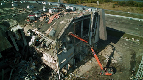 powerful excavator disassembles roof of ruined arena Live Action