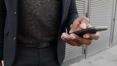 Businessman typing on cellphone on street.Professional using smartphone outdoors Live Action