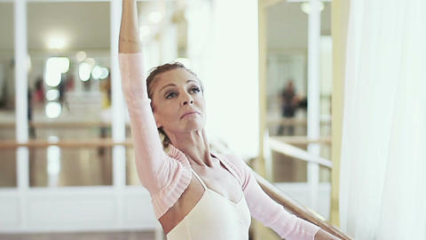 Elderly ballerina holds on to barre and practices ballet moves Footage