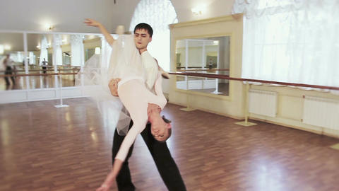Young male holds ballerina on shoulder and twirls her around Footage