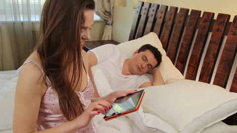 Couple in bedroom, girl watching photos on tablet, guy sleeping Footage