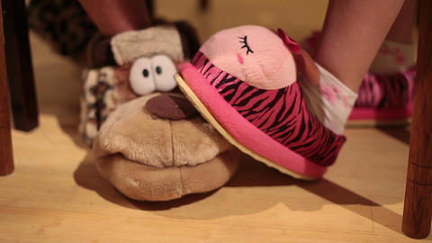 Couple's feet in funny novelty slippers playing under table Footage
