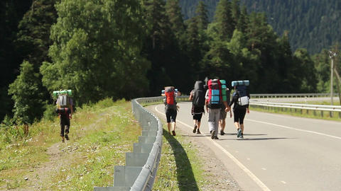 Group of tourists backpackers walking down the road, traveling Footage