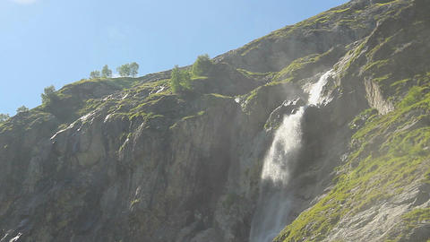 Beautiful waterfall in mountains, wind blows water spray around Footage