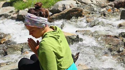 Female tourist praying near mountain river, Buddhism, relaxation Footage