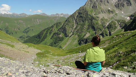 Female sitting in lotus position, doing yoga, mountain landscape Footage