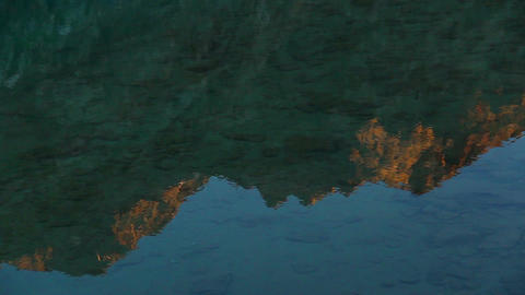 Reflection of mountain in clear water, sunset or sunrise, nature Footage