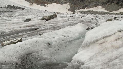Dirty melting snow, water stream running down the hill, spring Footage