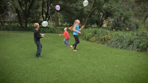 Three cute, young kids play together in a park with balloons in slowmo Footage