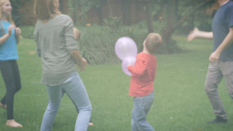 An entire family of five play together outside jumping and laughing - slowmo ste Footage