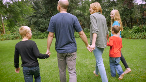 The camera follows a family of five holding hands walking together barefoot in t Footage