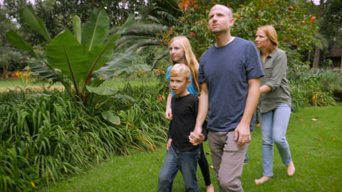 A family of 5 exploring a tropical garden together while holding hands - slowmo  Footage