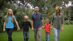 A father, mother, young daughter, and two young sons walking barefoot through th Footage