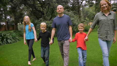 A smiling happy family of 5 look at and walk towards the camera - slowmo steadic Footage