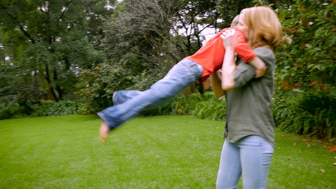 A young boy runs to his mother and she lifts him up and spins him around and the Footage
