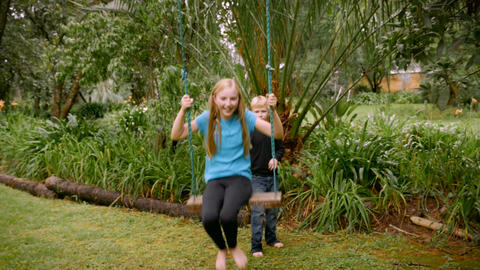 A young girl swings directly in front of the camera while her younger brother pu Footage