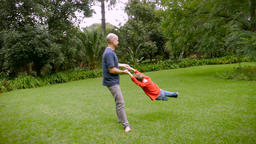 A father spins his 5 year old son around in circles on the grass - slowmo steadi Footage