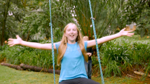 A tween girl opens her arms while swinging on a swing in slowmo with a younger b Live Action