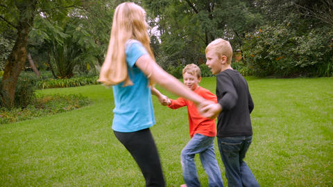 Three young children playing ring around the rosie - slowmo. The youngest child Footage