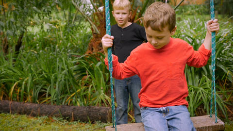 A young boy tries to get going on a swing by himself with another boy standing b Footage