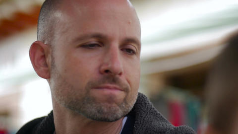 Profile of an attractive man with a slight beard and shaved head looking around Footage