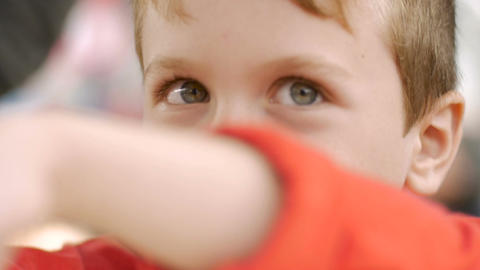 Close up of a young boy's eyes looking at the camera with his arm in front of hi Footage