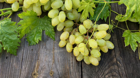 Bunch of white grapes with leaves on wooden table Footage