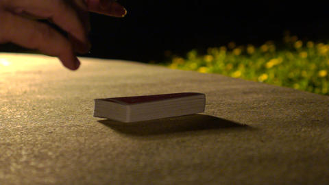Closeup Hand Takes Card Pack from Table under Backlight Footage