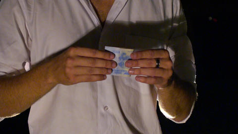 Closeup Hands Roll up Banknote for Trick against Darkness Footage