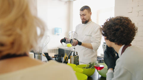 Cheerful cook teaching people in cookery school holding food talking wearing Live Action