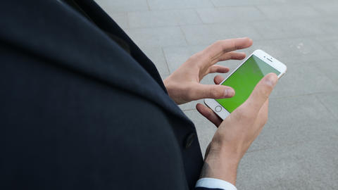 Businessman using cellphone on urban street. Worker scrolling smartphone outside Live Action
