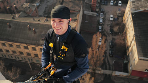 Close-up shot of cheerful and smiling man who is about to go down the wall Live Action