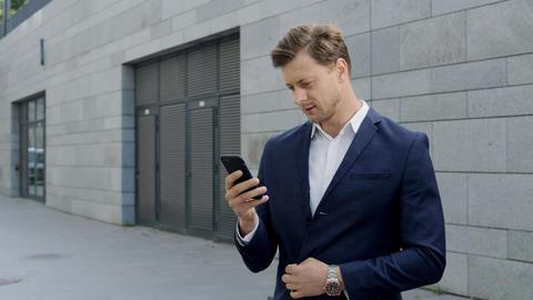 Businessman using smartphone at street.Entrepreneur celebrating victory outdoors Live Action