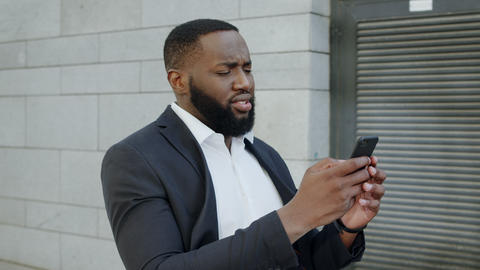 African businessman getting bad news on phone. Business man walking on street Live Action