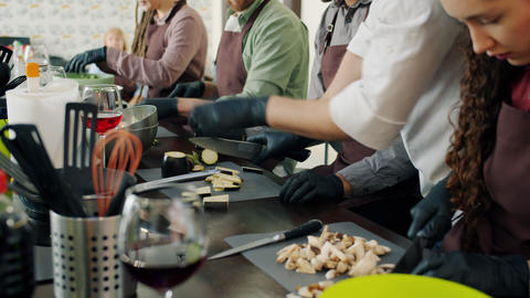 Young men and women mixed race group cooking food during cookery master-class Live Action