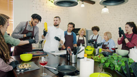 Cookery school students and male chef cooking meat dish together learning Live Action